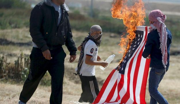 Palestinians burn a U.S flag at the Israel-Gaza border during a protest demanding the right to return to their homeland, east of Gaza City April 6, 2018