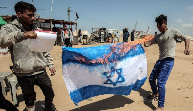 Palestinians protestors burn an Israeli flag at the site of a tent protest on the Israel-Gaza border east of Rafah in the southern Gaza Strip. April 9, 2018