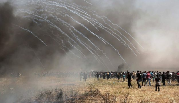 Tear gas fired by Israeli security forces passes through black smoke created by Palestinian protesters burning tires during clashes on the Gaza-Israel border east of Khan Yunis, Gaza. April 6, 2018