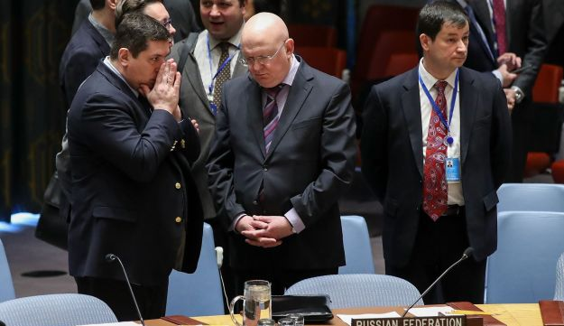 Deputy Russian Ambassador to the UN, Vladimir Safronkov, speaks with Russian Ambassador to the UN Vasily Nebenzya at the start of a Security Council meeting on the situation in Syria.