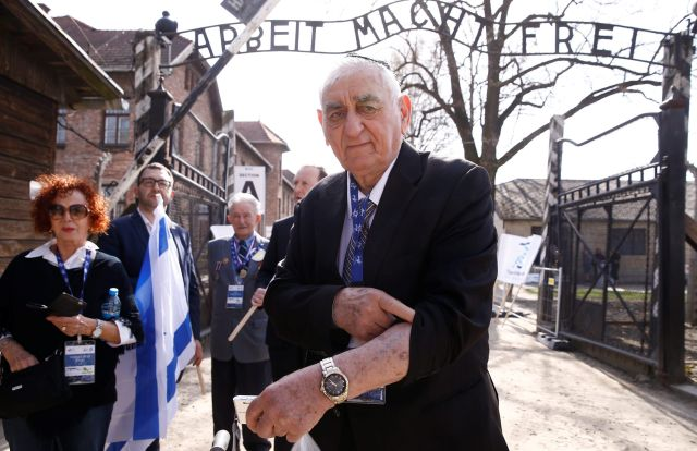 "Holocaust survivor Zoltan Matyah shows the number tattooed on his arm in front of the front of the ""Arbeit macht frei"" (Work sets you free) gate in the former Nazi death camp Auschwitz before the start of the annual ""March of the Living"" to commemorate the Holocaust in Oswiecim, Poland, April 12, 2018."