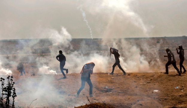 Palestinians take cover from tear gas smoke during clashes with Israeli security forces near border fence with Israel, east of Gaza City in the central Gaza Strip on April 13, 2018.