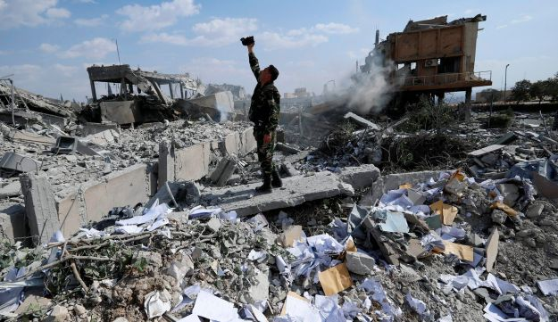 A Syrian soldier films the damage of the Syrian Scientific Research Center that was attacked by U.S., British and French airstrikes, April 14, 2018.