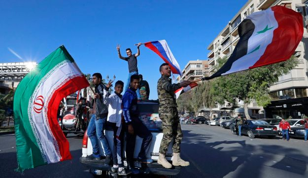 Syrian government supporters wave Syrian, Iranian and Russian flags and chant slogans against U.S. President Trump after awave of U.S., British and French military strikes. Damascus, Syria. April 14, 2018