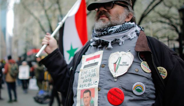 Demonstrators carry signs during an anti-war protest in New York after President Donald Trump launched airstrikes in Syria, April 15, 2018
