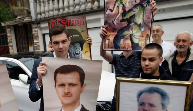 Serbian nationalists hold pictures of Syrian President Bashar Assad and the former Serbian leader and indicted war criminal Slobodan Milosevic to protest U.S. strikes on Syria. Belgrade, Serbia. April 15, 2018