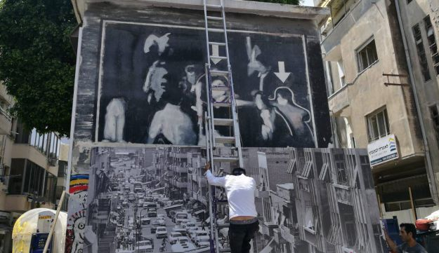 A photo being placed to cover up the mural. The photo was later removed