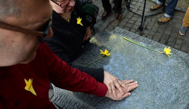 A man touches a monument when attending an independent ceremony in honor of the fighters of the 1943 Warsaw Ghetto Uprising on its 75th anniversary in Warsaw, Poland, Thursday, April 19, 2018.