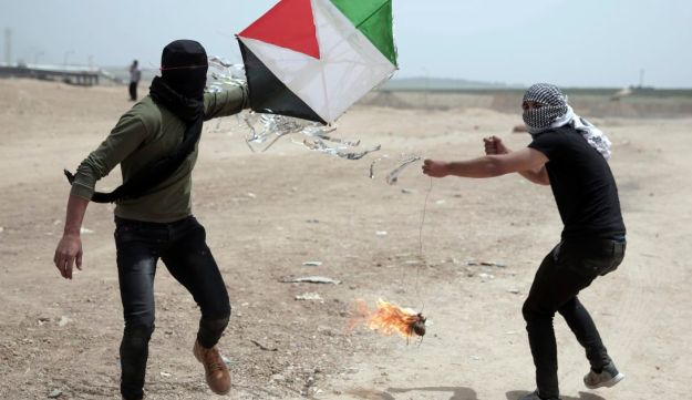 Palestinian protesters fly a kite with a burning rag dangling from its tail to during a protest at the Gaza Strip's border with Israel, Friday, April 20, 2018.