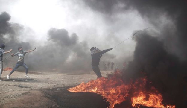 Palestinian protesters hurl stones at Israeli troops during a protest at the Gaza Strip's border with Israel, Friday, April 20, 2018.