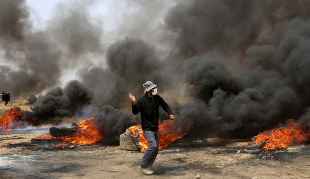 Palestinian protesters hurl stones at Israeli troops during clashes with Israeli troops along Gaza's border with Israel, east of Khan Younis, Gaza Strip, Friday, April 20, 2018.