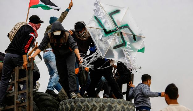 Palestinian protesters carry a transparent kite defaced with a swastika during clashes with Israeli forces across the border, April 20, 2018.