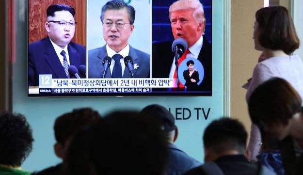 People watch a TV screen showing file footage of U.S. President Donald Trump, South Korean President Moon Jae-in and North Korean leader Kim Jong Un, during a news program at the Seoul Railway Station in Seoul, South Korea