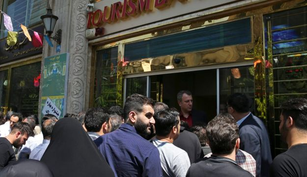 Iranians standing in front of a bank, hoping to buy U.S. dollars at the new official exchange rate announced by the government, in downtown Tehran, April 10, 2018.