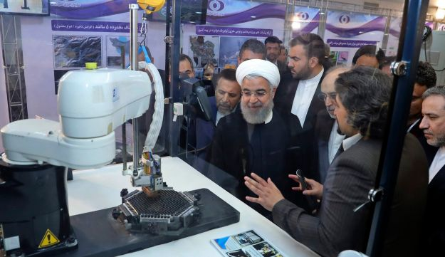 "Iranian President Hassan Rohani listening to explanations on new nuclear achievements at a ceremony to mark ""National Nuclear Day,"" in Tehran, April 9, 2018."