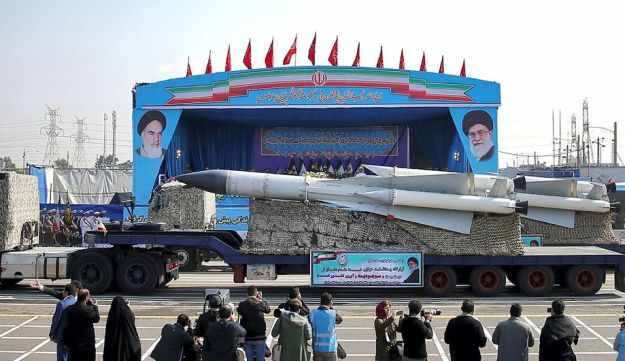In front of the portraits of supreme leader Ayatollah Ali Khamenei, right, and the late revolutionary founder Ayatollah Khomeini, left, a missile is displayed by Iran's army during a parade marking National Army Day at the mausoleum of Khomeini, just outside Tehran, Iran, Wednesday, April 18, 2018
