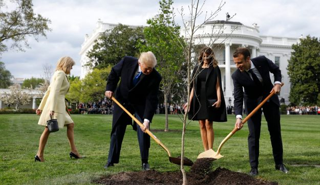 Brigitte Macron, France's first lady, from left, U.S. President Donald Trump, U.S. First Lady Melania Trump, and Emmanuel Macron, France's president, participate in a tree planting on the South Lawn of the White House in Washington, D.C., U.S., on Monday, April 23, 2018. As Macron arrives for the first state visit of Trumps presidency, the U.S. leader is threatening to upend the global trading system with tariffs on China, maybe Europe too. Photographer: Yuri Gripas/Bloomberg
