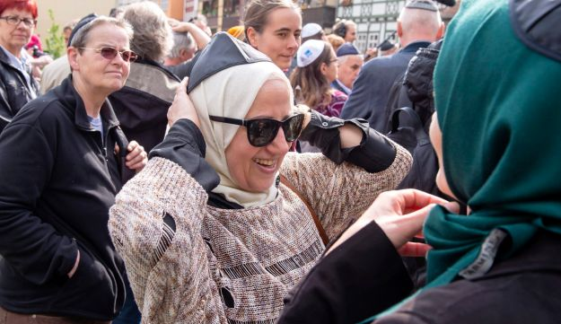 A Muslim woman puts a kippa over her headscarf during a demonstration against anti-Semitism in Erfurt, Germany, April 25, 2018.