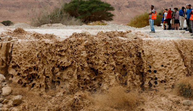 Israelis watch flooded water running through a valley blocking the main road along the Dead Sea in the Judean desert, near the desert fortress of Masada north of Ein Bokek, following heavy rainfall in the mountains on April 25, 2018. / AFP PHOTO / MENAHEM KAHANA