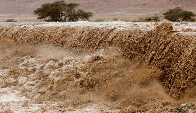 Israelis watch flooded water running through a valley blocking the main road along the Dead Sea in the Judean desert on April 25, 2018.