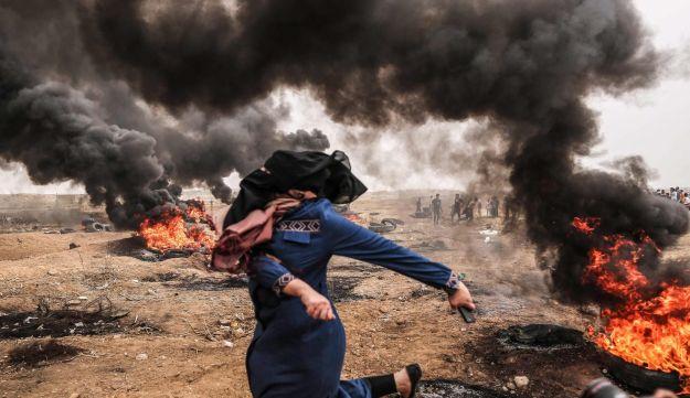 A Palestinian woman protester hurls stones towards Israeli forces during clashes along the border with the Gaza strip east of Gaza City, May 4, 2018.
