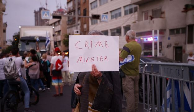 A protester holding a sign saying 'Crime Minister' in Tel Aviv, May 5, 2018.