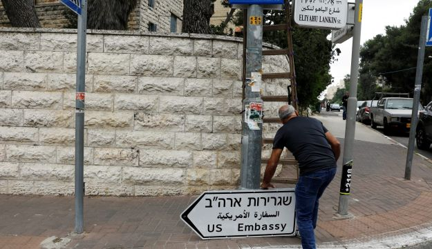 A worker holds a road sign directing to the U.S. embassy, in the area of the U.S. consulate in Jerusalem, May 7, 2018.