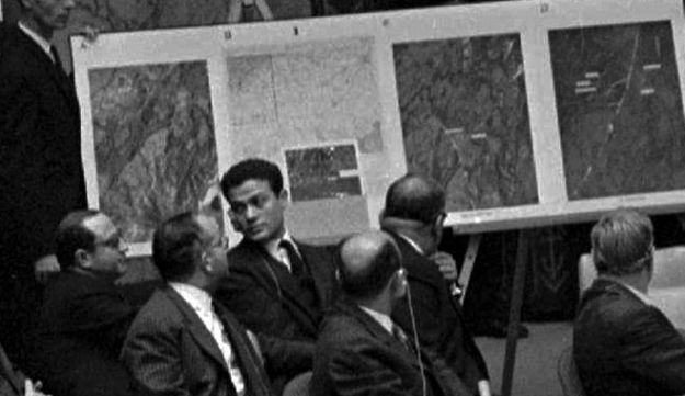 U.S. Ambassador Adlai E. Stevenson, far right, describes aerial photographs of Soviet missile launching sites in Cuba during a UN Security Council emergency session at the height of the Cuban Missile Crisis. Oct. 25, 1965