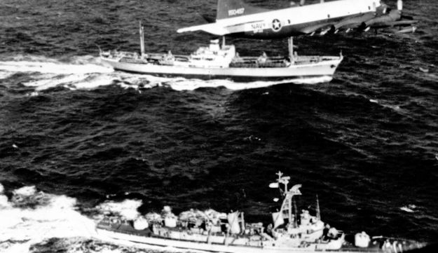 The U.S. destroyer Barry pulls alongside the Russian freighter Anosov, presumably carrying Soviet missiles withdrawn from Cuba, as a U.S. patrol plane flies overhead. November 10, 1962