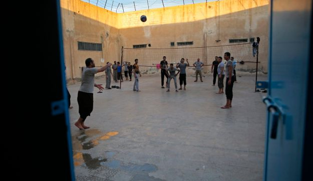 In this April 3, 2018 photo, prisoners play volleyball, in a Kurdish-run prison housing former members of the Islamic State group, in Qamishli, north Syria. After defeating IS in battle, Syriaג€™s Kurds are now eager to show they can bring justice against the groupג€™s members. The emphasis is on leniency and reconciliation with the aim of extending bridges to the Arabs they now rule and winning international legitimacy.