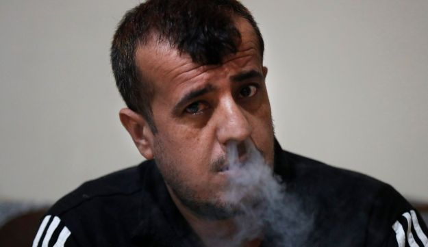 In this April 3, 2018 photo, Abdullah Khalaf, 35, a Syrian former member of the Islamic State group, smokes during an interview with The Associated Press, at a Kurdish-run prison housing former members of the Islamic State group, in Qamishli, north Syria. Khalaf is serving a 20-year sentence for his role in an attack in 2016 that killed 10 people in a town in northern Syria. After defeating IS in battle, Syriaג€™s Kurds are now eager to show they can bring justice against the groupג€™s members.