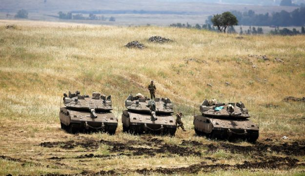 An Israeli soldier stands on a tank as another jumps off it near the Israeli side of the border with Syria in the Golan Heights, Israel May 9, 2018. REUTERS/Amir Cohen
