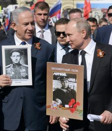Prime Minister Benjamin Netanyahu and Russian President Vladimir Putin hold portraits of their relatives who fought in World War II, on Victory Day, Moscow, May 9, 2018.