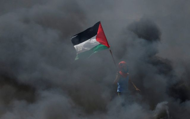 A boy holds a Palestinian flag during a protest at the Israel-Gaza border, May 14, 2018