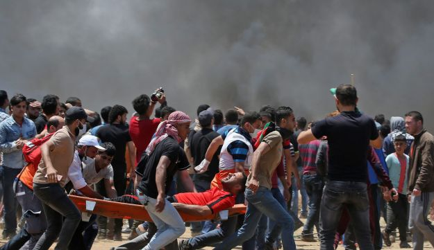 Palestinian men carry an injured protester during clashes with Israeli forces near the Gaza border, May 14, 2018