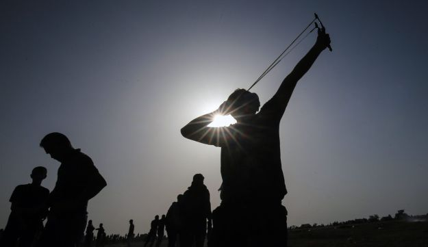 A Palestinian demonstrator uses a slingshot during clashes with Israeli forces along the border with the Gaza strip east of Khan Yunis on May 18, 2018