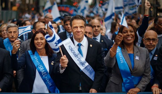 New York Gov. Andrew Cuomo, center, honorary grand marshal, joins other dignitaries as they march along Fifth Avenue during the annual Celebrate Israel parade, Sunday, June 3, 2018, in New York. (AP Photo/Andres Kudacki)
