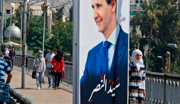 Pedestrians walk past a portrait of Syrian President Bashar Assad hanging in a street in the Syrian capital Damascus on May 31, 2018