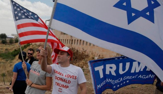 Israelis hold American and Israeli flags with the new U.S. embassy in the background in Jerusalem,  May 14, 2018.