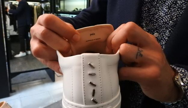 Syrian designer Daniel Essa shows the word Paix (Peace) printed on his luxury sneakers during an interview at a concept store in Lille, France, June 6, 2018.