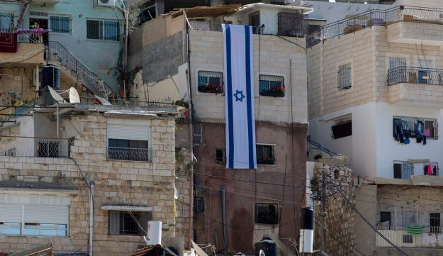 An Israeli flag hangs on the wall of a building that was taken over by settlers in the East Jerusalem neighborhood of Silwan.