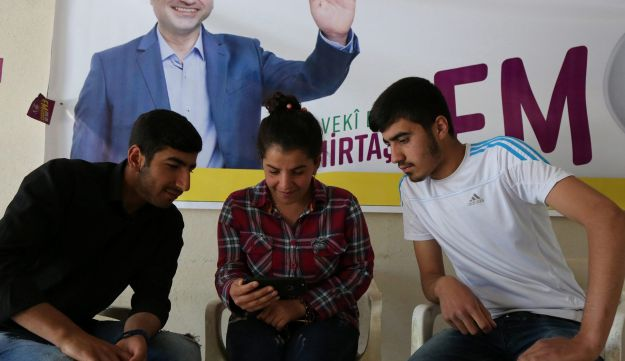 People watching a video announcing the first election rally of Selahattin Demirtas, jailed former leader of pro-Kurdish opposition Peoples' Democratic Party (HDP), in an election office of HDP in Mardin province, Turkey, June 6, 2018.
