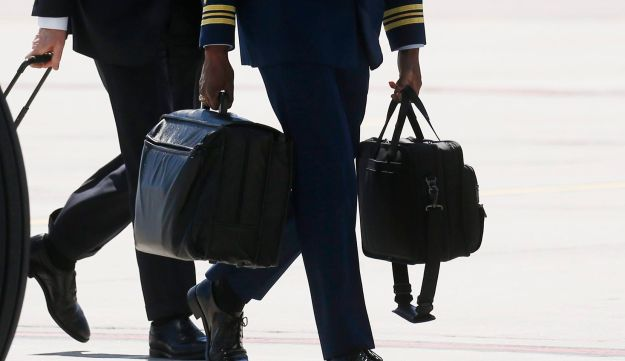 """A U.S. military aide carrying the """"nuclear football"""" walks from Air Force One as President Donald Trump arrives in La Baie, Canada ahead of the G7 Summit, June 8, 2018."""
