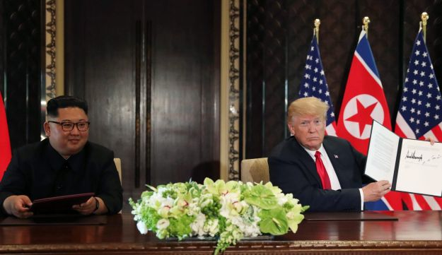 Trump signs an agreement with Kim Jong Un after their meeting at Capella Hotel in Singapore, June 12, 2018.