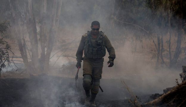 An Israel soldier extinguishes a fire started by a kite launched by Palestinians from Gaza, near the Israel and Gaza border, Friday, June 1, 2018.
