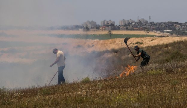 Israeli workers of Nature and Parks Authority extinguish a fire started by a kite launched by Palestinians from Gaza, Tuesday, June 5, 2018.