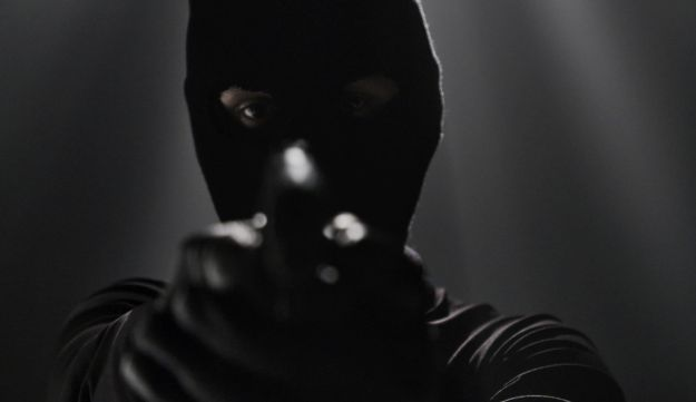 """A screenshot from the documentary """"Who Shot the Barnoar Kids?"""" showing a masked man aiming a gun."""