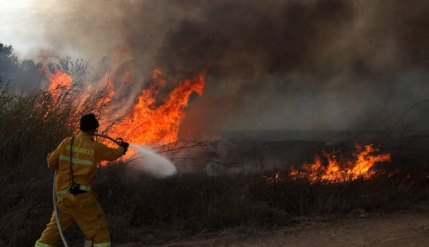 An Israeli firefighter puts out a fire sparked by incendiary kites sent from Gaza, Eshkol Regional Council, southern Israel, June 18, 2018.