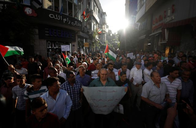Palestinians take part in a protest calling on Abbas to lift the sanctions on Gaza Strip, in Ramallah, June 23, 2018.