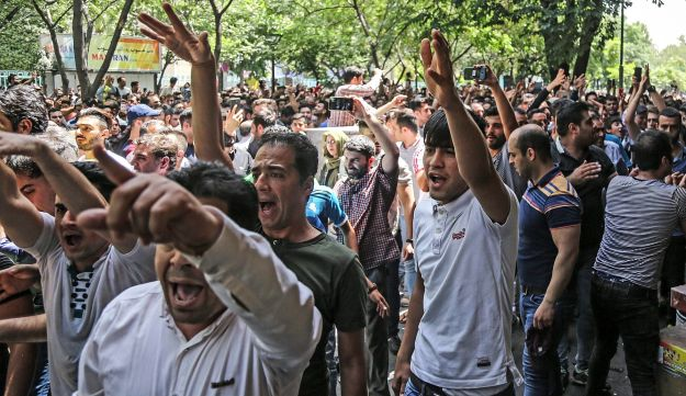 A group of protesters chant slogans at the old grand bazaar in Tehran, Iran, Monday, June 25, 2018